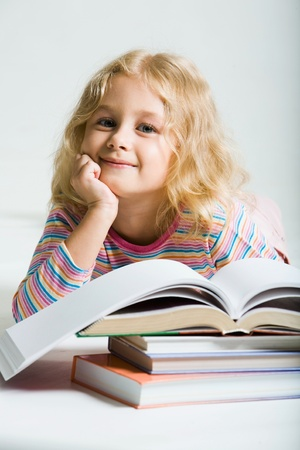 Beautiful smiling schoolgirl is lying beside  books on a white background photo