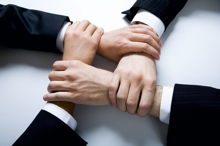 MEMBERSHIP: Isolated on white four crossed human hands in business wear