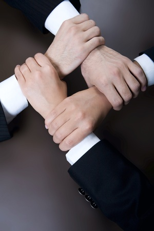 MEMBERSHIP: Isolated on black four crossed human hands in business wear