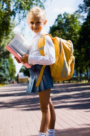 First-former girl is going to school carrying backpack and holding a book Stock Photo - 8314267