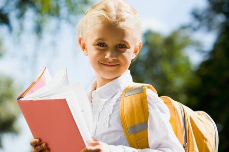 Portrait of happy young schoolgirl looking at camera photo