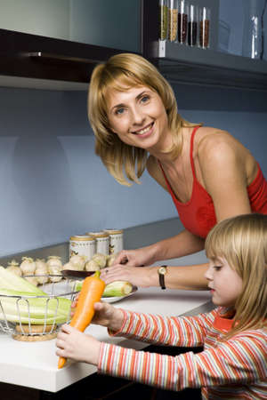 Portrait of a young woman in the kitchen cutting vegetables with her little daughter holding carrot  near by  photo