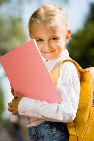 Portrait of smiling adorable girl with backpack holding a book outside photo