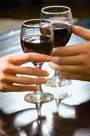 Symbolic picture of glasses of red wine in human hands photo