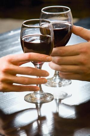 Imagen simbólica de vasos de vino tinto en manos humanas