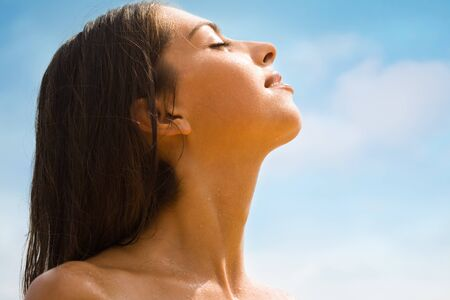 wet hair: Photo of profile of beautiful woman enjoying a sun   Stock Photo