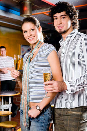 Portrait of young couple standing and holding the glasses of white wine  photo