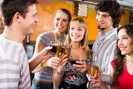Four people gazing at handsome man pronouncing a toast Stock Photo - 8314282