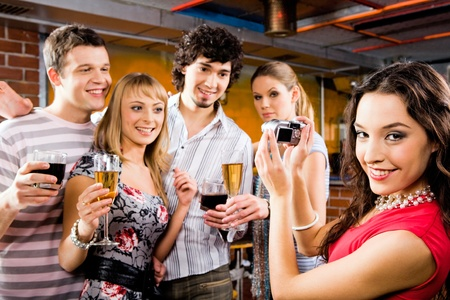 holiday gathering: Image of beautiful smiling woman holding the camera at the evening-party