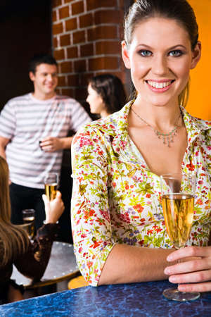 Portrait of smiling girl  with alcoholic drink in a night club Stock Photo - 8314231