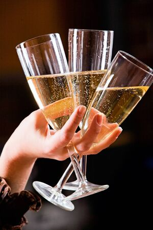 holydays: The glasses of champagne in the hand on the black background