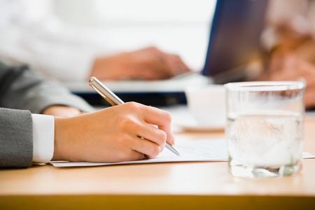 cuadro sinoptico: Mano mujer firme el documento sobre la mesa con un vaso de agua sobre el mismo