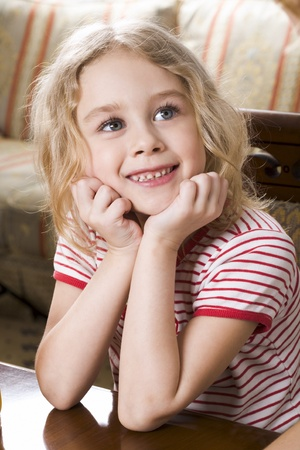 Smiling blond girl in stripe t-shirt sitting at the coffee table photo
