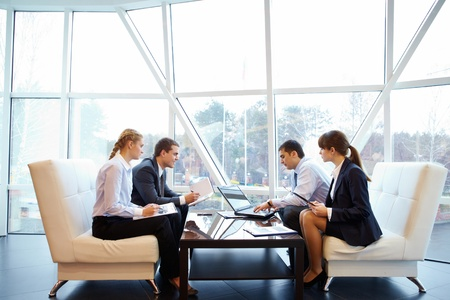 office documents: Photo of confident partners interacting at meeting in office Stock Photo