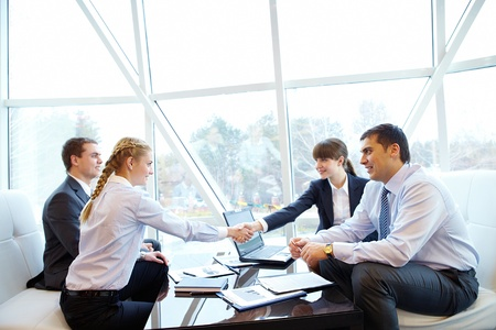 discussing: Photo of confident partners handshaking at meeting after making an agreement
