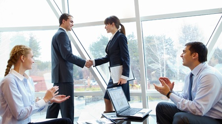 company: Photo of confident partners handshaking at meeting after making an agreement