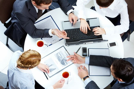 briefing: Image of business people hands working with papers and typing at meeting Stock Photo
