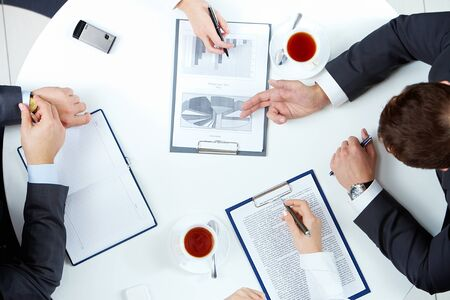 Image of business people hands working with papers at meeting photo