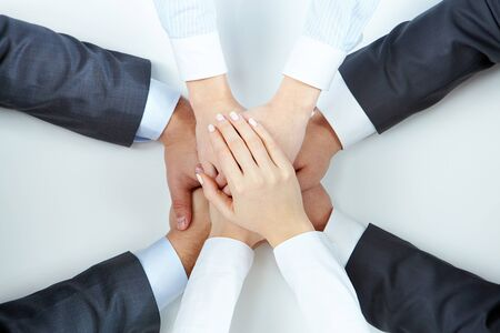 Image of business people hands on top of each other symbolizing support and power photo