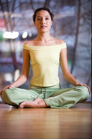 Relaxed young beautiful girl sitting in a lotus pose doing her exercise photo