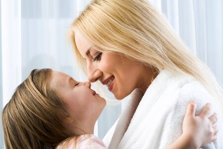 fondling: Little blond girl hugging her smiling mother reaching to kiss her
