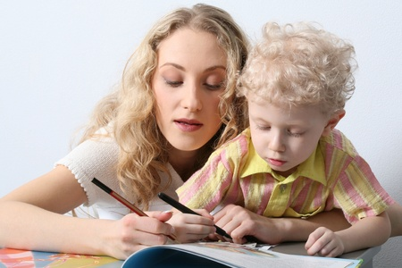Beautiful mother and her smart son are painting together  photo