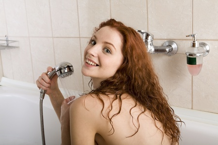 Young woman with red hair in the bath douching herself photo