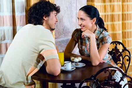 Young couple are sitting at the table and looking at each other Stock Photo - 8357223