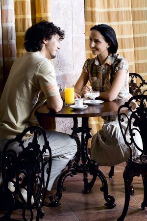daremny: MÅ'oda para w starych cafe siedzi na tabelÄ™, mówi, jedzenie lody Å›mietankowe i pije sok Zdjęcie Seryjne