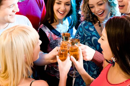 Group of champagne flutes in people�s hands making a toast  Stock Photo - 8357212