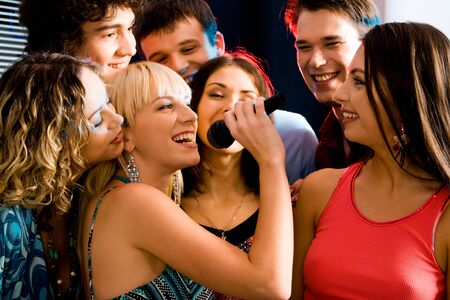 people partying: Pretty woman sings a song in the environment of her friends at a karaoke party