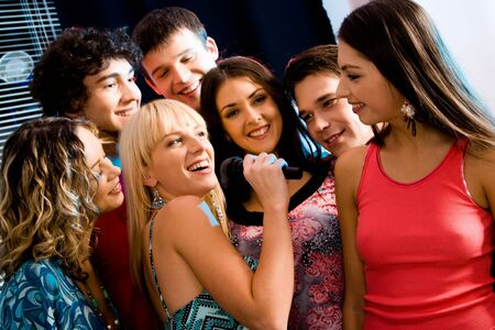 Six people listen to singing of their girlfriend at a karaoke party photo