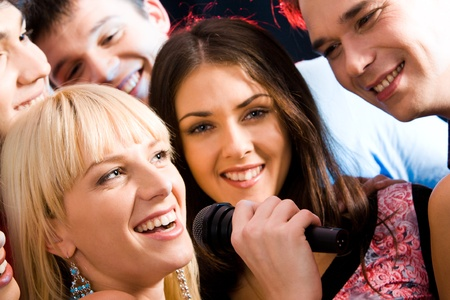 Image of woman singing with her friends at a karaoke party photo