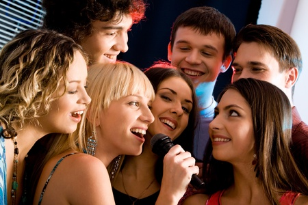 Attractive woman is holding the microphone and singing with friends   Stock Photo