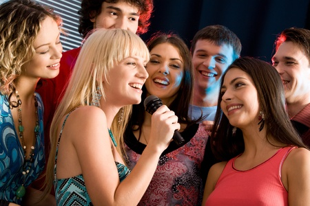 Portrait of seven young attractive friends at a karaoke party photo