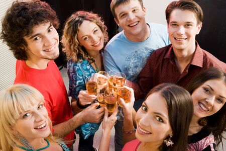 Portrait of happy young friends touching the glasses with each other Stock Photo - 8357307