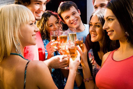 Portrait of happy young friends touching the glasses with each other Stock Photo - 8357249