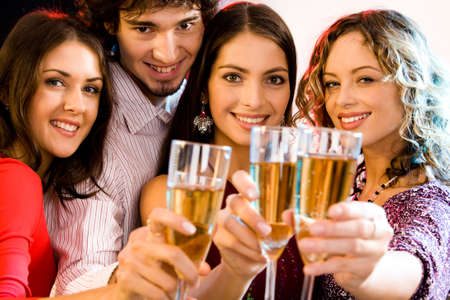 Portrait of four people holding glasses of  champagne, photo