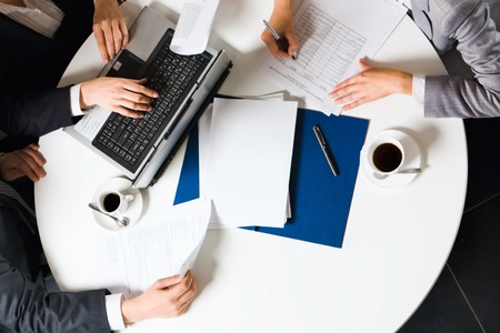 round table: Human hands holding pens and papers, making notes in documents, typing on the lap top placed on the table with two cups of coffee on it