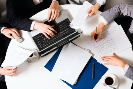 Human hands holding pens and papers, making notes in documents, typing on the lap top placed on the table with two cups of coffee on it Stock Photo - 8357106