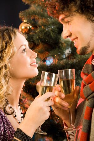 Portrait of amorous couple holding the glasses of champagne at christmas photo