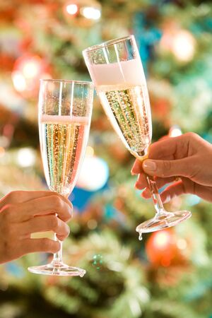 Image of two glasses of champagne in the hand on the background of christmas- tree photo