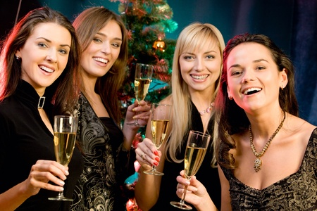 Portrait of four woman holding the glasses of champagne on the background of christmas-tree photo
