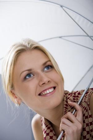 Lovely girl under umbrella smiling photo