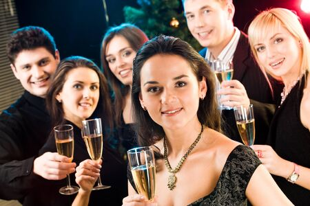 Beautiful woman raising up her glass on the background of five friends Stock Photo - 8357191
