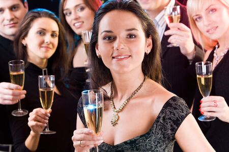Fascinating woman is holding the alcoholic drink on the background of her friends  Stock Photo - 8357203