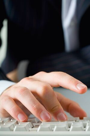 Close-up of male fingers typing on the keyboard photo