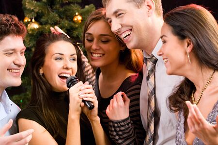 people singing: Portrait of several people singing a song together at a karaoke party