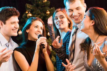 Portrait of five friends having fun at karaoke party photo