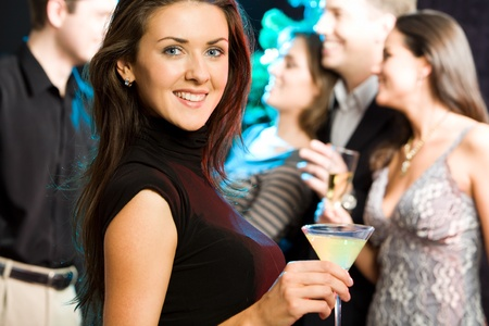 Young friendly woman looking at camera while a party photo
